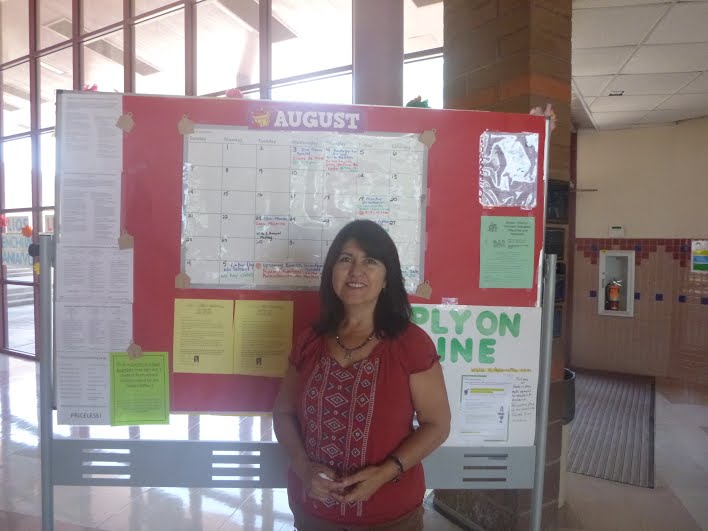Mrs. Marin-Varelas standing in front of an announcement board