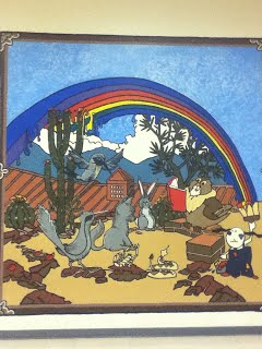 Animals Gathered around to hear a story in a courtyeard under a rainbow